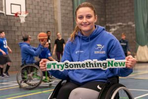 Young woman in sports wheelchair with basketball court in background holds green sign whiich reads 'Try something new'