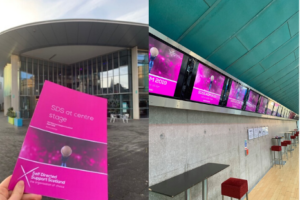 SDSS AGM Programme held in front of Perth Concert Hall and a row of plasma screens showing SDSS logo